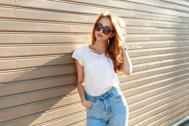 stylish pretty hipster woman in sunglasses and vintage high waist jeans leaned against on the wooden wall - hohe taille jeans stock-fotos und bilder