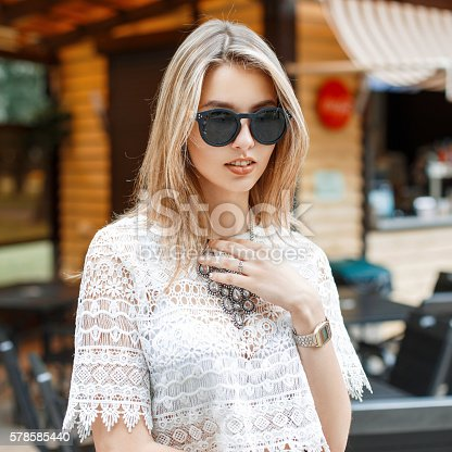578791454istockphoto Stylish pretty woman in white lace blouse and sunglasses 578585440