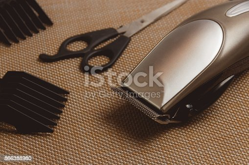 866388950istockphoto Stylish Professional Hair Clippers, accessories on brown background 866388980