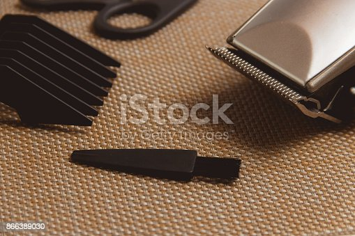 866388950istockphoto Stylish Professional Hair Clippers, accessories on brown background 866389030
