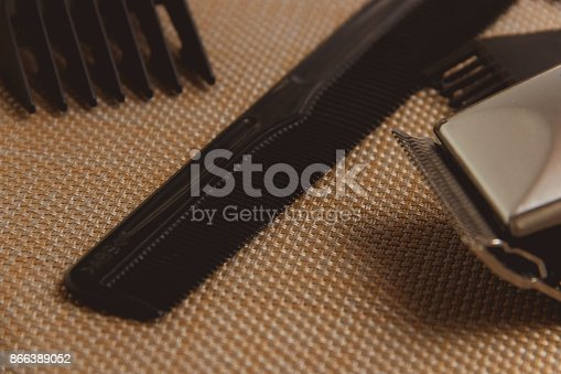 866388950istockphoto Stylish Professional Hair Clippers, accessories on brown background 866389052