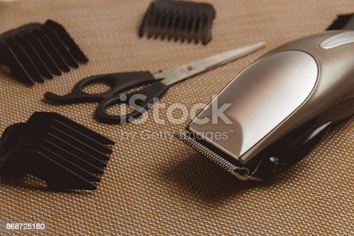 866388950istockphoto Stylish Professional Hair Clippers, accessories on brown background 868725180