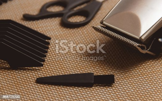 866388950istockphoto Stylish Professional Hair Clippers, accessories on brown background 868725200