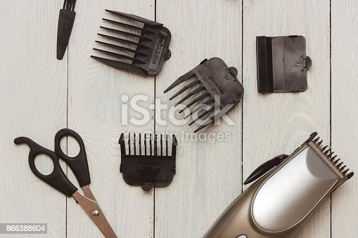 868725110istockphoto Stylish Professional Hair Clippers, accessories on wood background 866388604