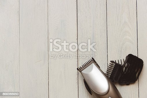868725110istockphoto Stylish Professional Hair Clippers, accessories on wood background copy space 866388650