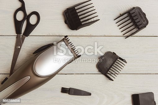868725110istockphoto Stylish Professional Hair Clippers, accessories on wood background 866388656