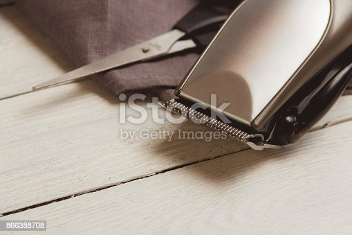 868725110istockphoto Stylish Professional Hair Clippers, accessories on wood background copy space 866388708