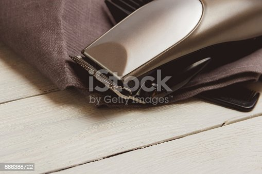 868725110istockphoto Stylish Professional Hair Clippers, accessories on wood background copy space 866388722