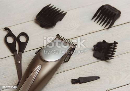 868725110 istock photo Stylish Professional Hair Clippers, accessories on wood background 868725098