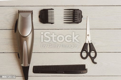 868725110istockphoto Stylish Professional Hair Clippers, accessories on wood background copy space 868725110