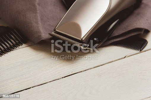 868725110 istock photo Stylish Professional Hair Clippers, accessories on wood background copy space 868725116