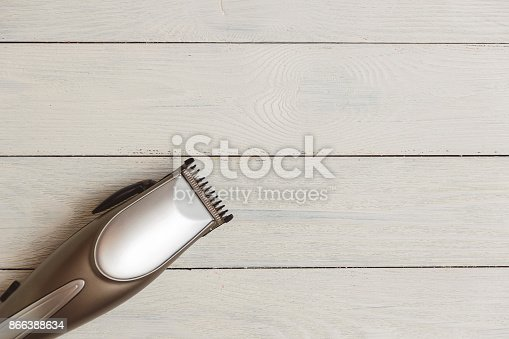868725110istockphoto Stylish Professional Hair Clippers on wood background with copy space 866388634
