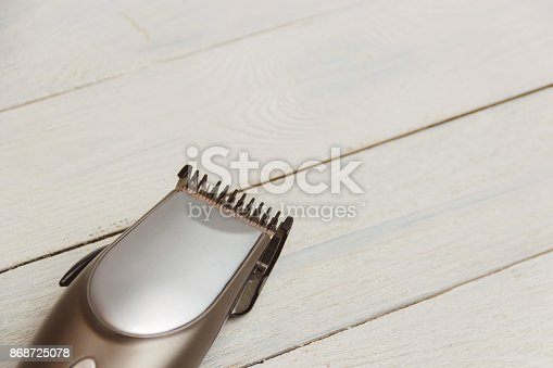 868725110istockphoto Stylish Professional Hair Clippers on wood background with copy space 868725078