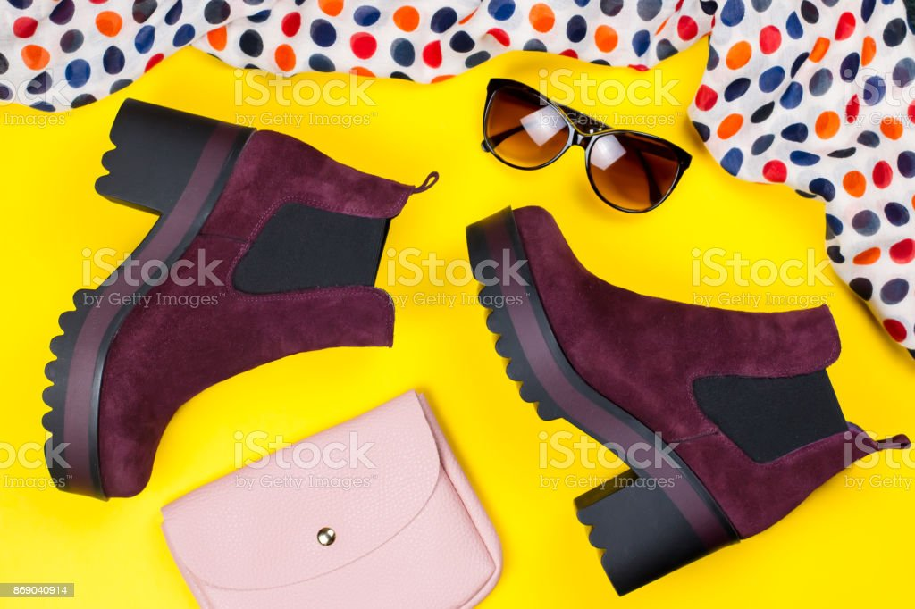 Stylish purple suede ankle boots, pink purse, sunglasses and printed scarf stock photo