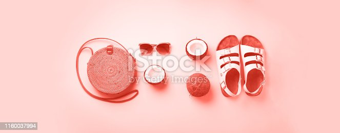 1078252566 istock photo Stylish rattan bag, coconut, birkenstocks, palm branches, sunglasses on coral color background. Top view with copy space. Trendy bamboo bag and white shoes. Summer fashion flat lay 1160037994