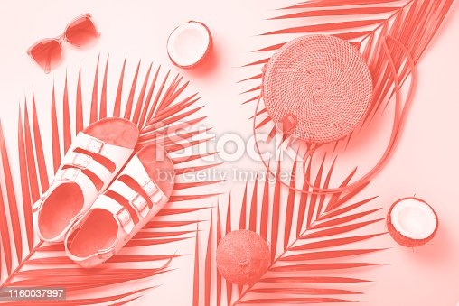 1078252566 istock photo Stylish rattan bag, coconut, birkenstocks, palm branches, sunglasses on coral color background. Top view with copy space. Trendy bamboo bag and white shoes. Summer fashion flat lay 1160037997