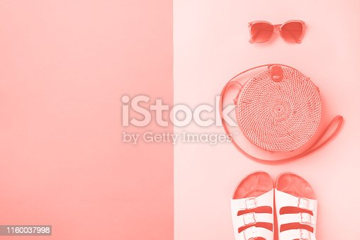 1078252326 istock photo Stylish rattan bag, coconut, birkenstocks, palm branches, sunglasses on coral color background. Top view with copy space. Trendy bamboo bag and white shoes. Summer fashion flat lay 1160037998
