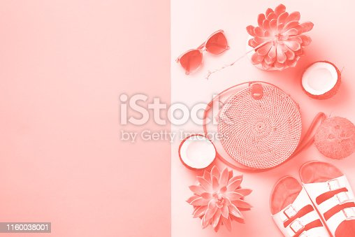 1078252566 istock photo Stylish rattan bag, coconut, birkenstocks, palm branches, sunglasses on coral color background. Top view with copy space. Trendy bamboo bag and white shoes. Summer fashion flat lay 1160038001