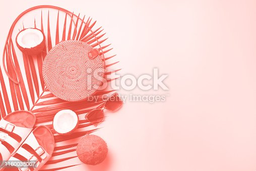 1078252566 istock photo Stylish rattan bag, coconut, birkenstocks, palm branches, sunglasses on coral color background. Top view with copy space. Trendy bamboo bag and white shoes. Summer fashion flat lay 1160038007