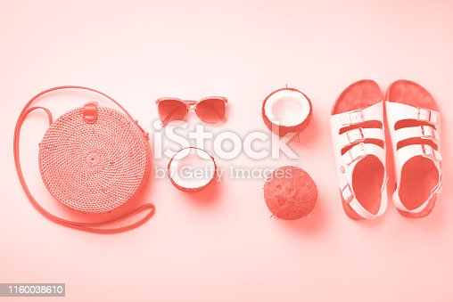 1078252326 istock photo Stylish rattan bag, coconut, birkenstocks, palm branches, sunglasses on coral color background. Top view with copy space. Trendy bamboo bag and white shoes. Summer fashion flat lay 1160038610