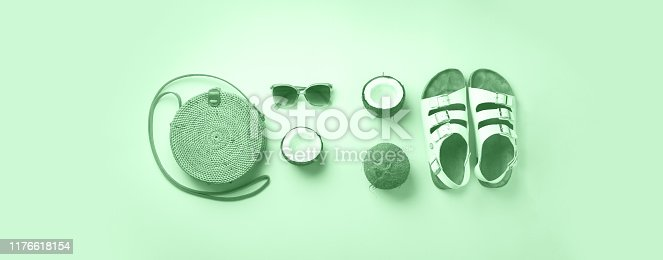1078252566 istock photo Stylish rattan bag, coconut, birkenstocks, palm branches, sunglasses on mint color background. Top view with copy space. Trendy bamboo bag and white shoes. Summer fashion flat lay 1176618154
