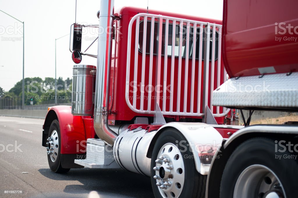 Stylish red big rig semi truck with day cab and safety guard against possible displacement of the load during braking and with red trailer on the highway stock photo