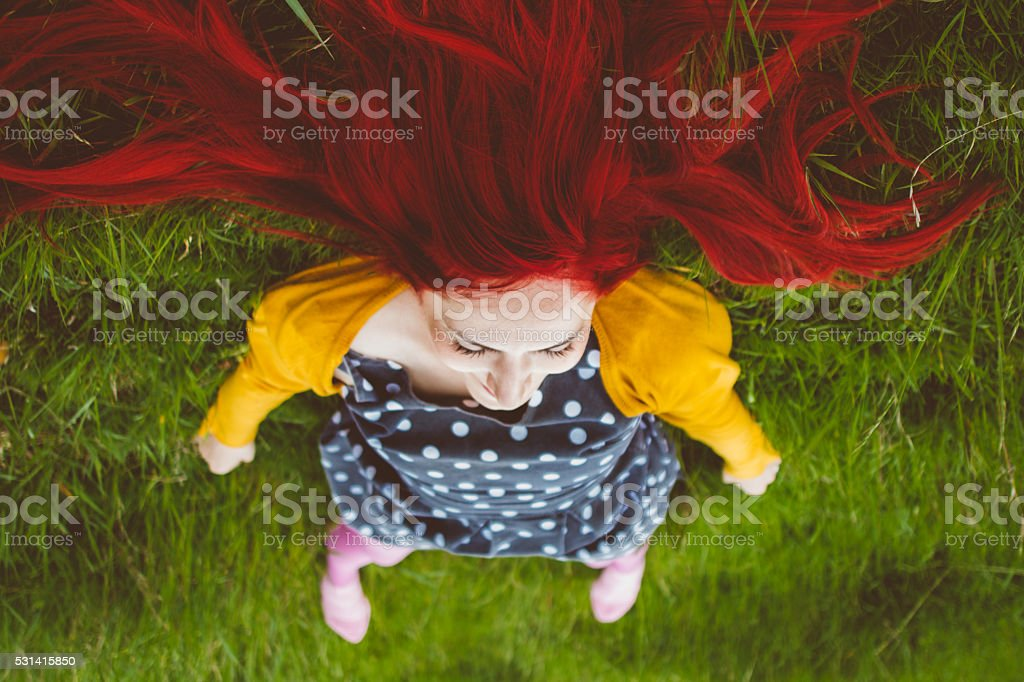 Portrait of joyous young red haired woman laying in grass from the...