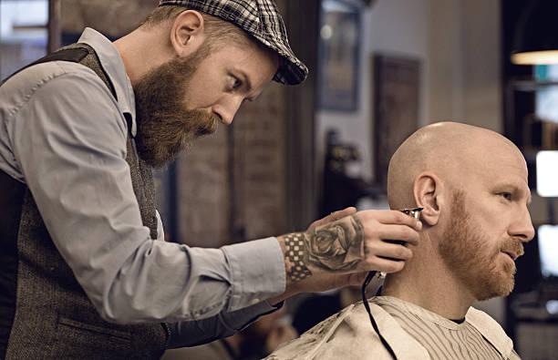 stilvoller retro-bärtiger friseur mit einem bärtigen männlichen kunden glatze - glatze schneiden stock-fotos und bilder
