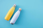 Stylish reusable eco-friendly stainless steel thermo bottles on light blue background. Space for text. Zero waste, plastic free and sustainable lifestyle concept. Top view, flat lay.