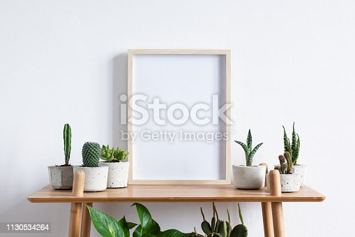 istock Stylish room interior with mock up photo frame on the brown bamboo shelf with beautiful plants in differents hipster and design pots. White walls. Modern and floral concept of shelfs. 1130534264