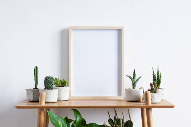 Stylish room interior with mock up photo frame on the brown bamboo shelf with beautiful plants in differents hipster and design pots. White walls. Modern and floral concept of shelfs. stock photo