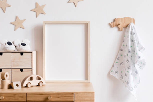 Stylish scandi childroom withwooden mock up photo frame, wooden toys, boxes, blocks and accessories Stars pattern on the background wall. Bright and sunny interior with wooden desk. Home decor. stock photo