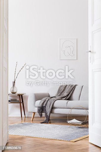 istock Stylish scandi interior of home space with design grey sofa and retro small table. Living room with design accessories and mock up poster frame. Elegant decor. Brown wooden parquet with modern carpet. 1138635675