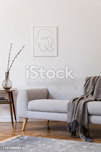 istock Stylish scandi interior of home space with design grey sofa and retro small table. Living room with design accessories and mock up poster frame. Elegant decor. Brown wooden parquet with modern carpet. 1141409483