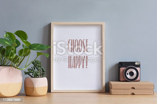 istock Stylish scandi interior with mock up photo frame on the brown wooden table with instant camera, paper boxes and plants in design pots. Grey walls. Minimal concept of mockup. 1126975991