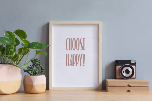 인스턴트 카메라, 종이 상자와 식물 디자인 냄비에 갈색 나무 테이블에 사진 프레임을 모의로 세련 된 스캔 디 인테리어. 회색 벽입니다. 이랑의 최소한의 개념입니다. - 건설 프레임 뉴스 사진 이미지