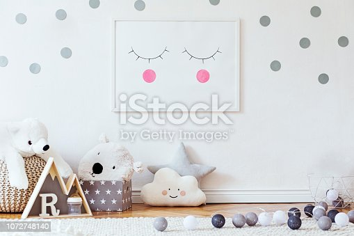 istock Stylish scandinavian child room with mock up photo poster frame on the pattern wall, boxes, teddy bear and toys.Cute modern interior of playroom with white walls, wooden accessories and colorful toys. 1072748140
