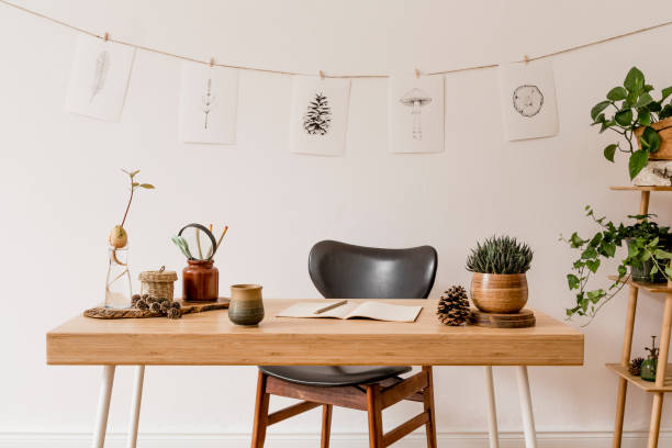 Stylish scandinavian home interior of open space, with a lot of plants, design accessories, bamboo shelf, wooden desk and hanging mock up forest drawings . Botany concept of home decor. Sunny room. stock photo