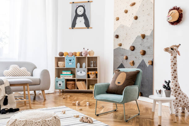 Stylish scandinavian interior design of childroom with gray sofa, modern climbing wall for kids, design furnitures, soft toys, teddy bear and cute children's accessories. Home decor. Template. stock photo