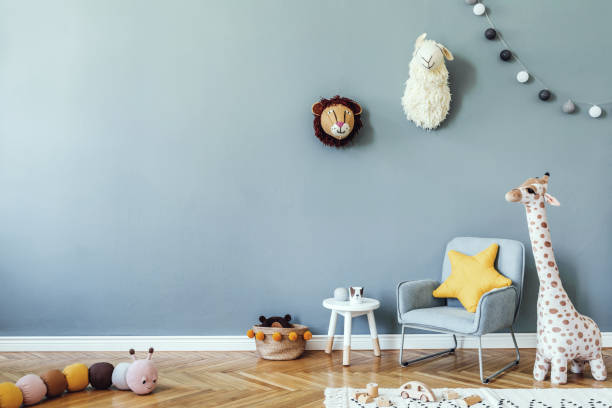 Stylish scandinavian kid room with toys, teddy bear, plush animal toys, mint armchair, cotton balls. Modern interior with eucalyptus background walls, Design interior of childroom. Template stock photo