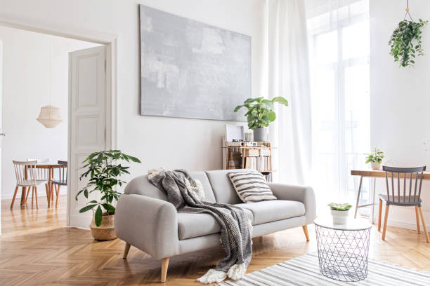 Stylish scandinavian living room with design furniture, plants, bamboo bookstand and wooden desk. Brown wooden parquet. Abstract painting on the white wall. Nice apartment. Modern decor of bright room stock photo
