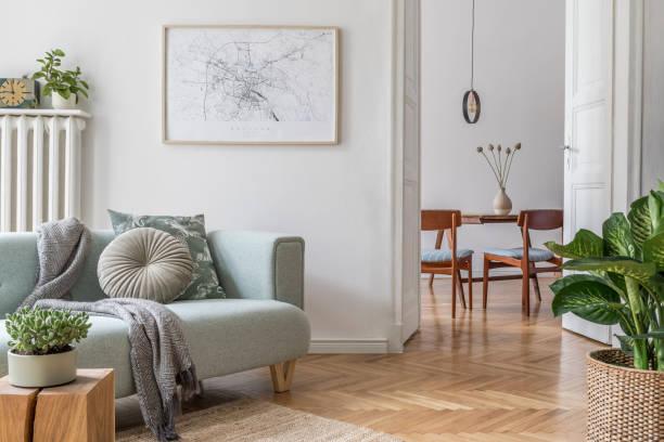 時尚的斯堪的納維亞客廳,配有設計薄荷床、傢俱、類比海報地圖、植物和優雅的個人配飾。現代家居裝飾。帶用餐室的開放式空間。範本可供使用。 - 室內 個照片及圖片檔
