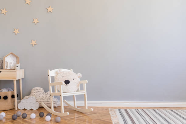 Stylish scandinavian newborn baby room with toys, children's chair, natural basket with teddy bear and small shelf. Modern interior with grey background walls, wooden parquet and stars pattern. stock photo