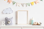 Stylish and modern scandinavian newborn baby interior with mock up photo or poster frame on the white shelf.