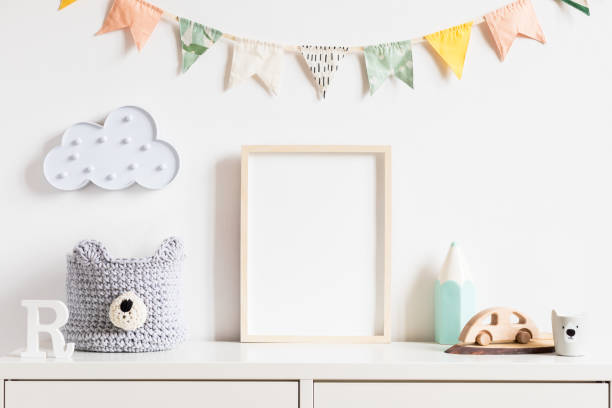 Stylish scandinavian newborn baby room with toys, teddy bear, accessories, ,cloud,colorful cotton flags and natural basket. Modern interior with mock up photo or poster frame. Real photo. Template. stock photo