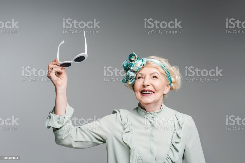 stylish senior woman holding vintage sunglasses isolated on grey zbiór zdjęć royalty-free