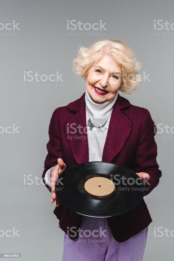 stylish senior woman holding vinyl disc isolated on gray background zbiór zdjęć royalty-free