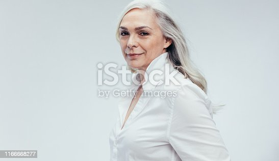 Elegant senior woman standing against white background. Stylish mature woman in white casuals.
