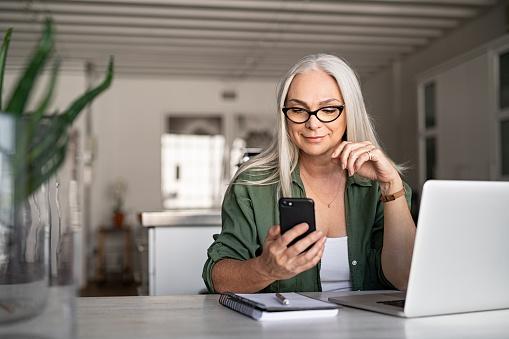 Stylish senior woman messaging with phone