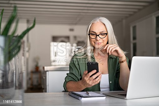 Happy senior woman using mobile phone while working at home with laptop. Smiling cool old woman with white hair wearing eyeglasses sitting on chair at table and messaging with smartphone. Beautiful stylish elderly lady browsing site on cellphone.
